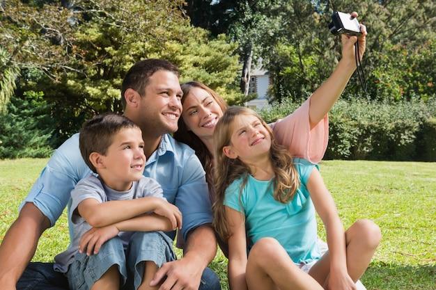Glimlachende familie in een park dat foto's neemt