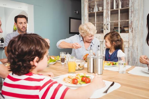 Glimlachende familie met grootouders die bij eettafel zitten