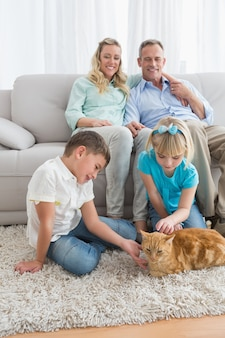 Glimlachende familie met hun gemberkat op de deken