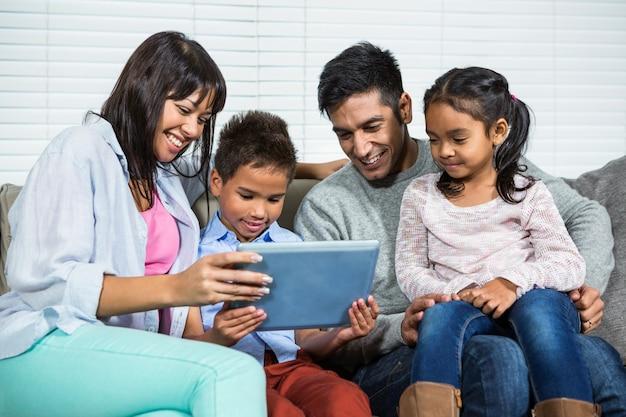 Glimlachende familie op de bank die tablet gebruikt