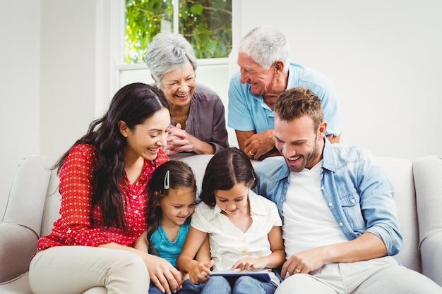 Glimlachende familie van meerdere generaties die een tablet gebruiken