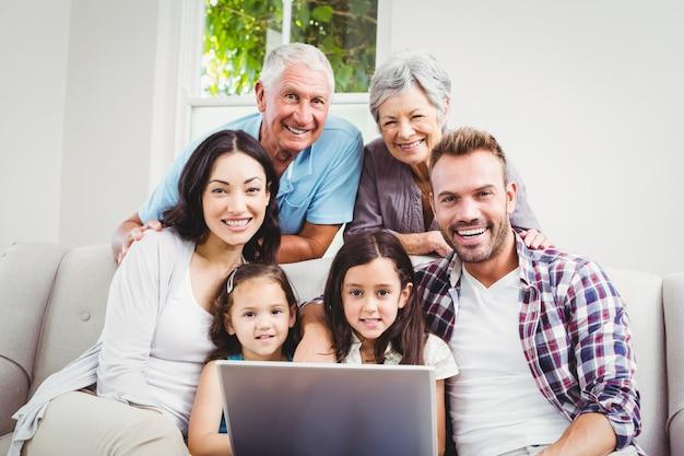 Glimlachende familie van meerdere generaties die laptop met behulp van