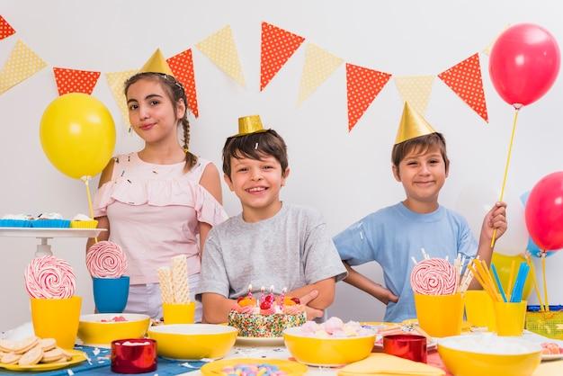 Glimlachende feestvarken met zijn vrienden die verjaardag van partij genieten
