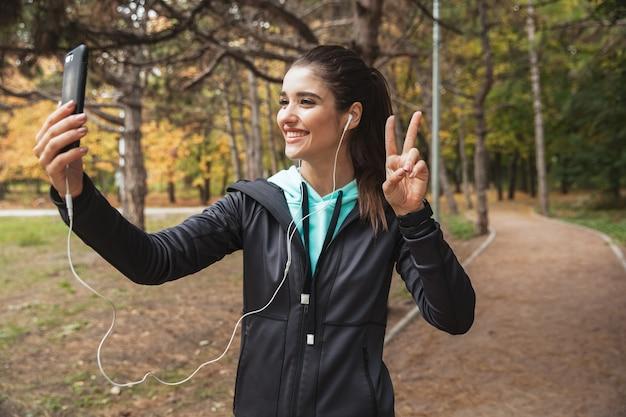 Glimlachende fitness vrouw luisteren naar muziek met koptelefoon, een selfie nemen terwijl je in het park staat