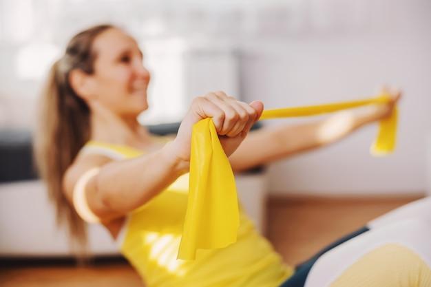Glimlachende fitte sterke sportvrouw die thuis op de vloer zit en krachtrubber met handen uitrekt.