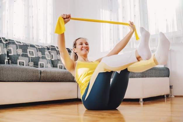 Glimlachende fitte sterke sportvrouw zittend op de vloer thuis en het uitrekken van machtsrubber met handen