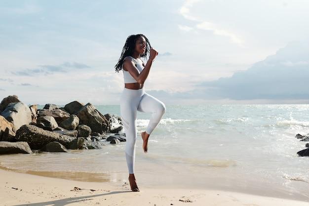 Glimlachende fitte vrouw die springoefening doet op zandstrand, prachtige rotsen en zeegolven op de achtergrond
