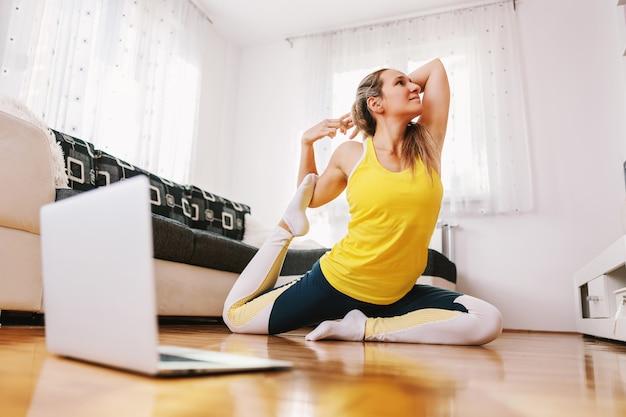 Glimlachende flexibele yoga-instructeur zittend op de vloer thuis in koning duif yoga pose en online tonen via laptop.