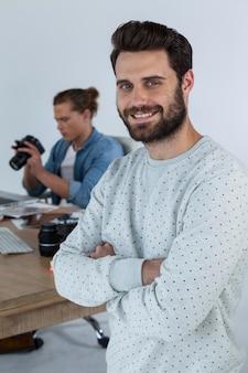 Glimlachende fotograaf die zich met zijn wapens bevinden die in studio worden gekruist