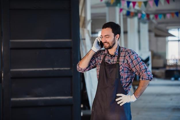 Glimlachende gebaarde mens die handschoenen, eigenaar van een klein houtbewerkingsbedrijf dragen, die zich in zijn workshop bevinden, die op mobiele telefoon spreken