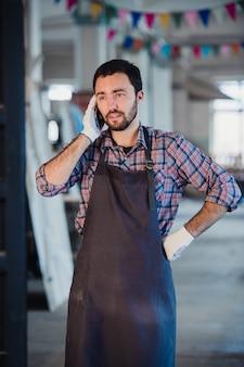 Glimlachende gebaarde mens die handschoenen, eigenaar van een klein houtbewerkingsbedrijf dragen, die zich in zijn workshopstudio bevinden, op mobiele telefoon spreken