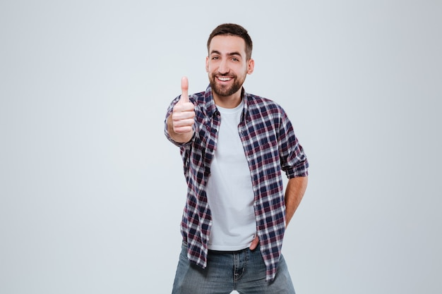 Glimlachende gebaarde mens in overhemd die duim tonen bij