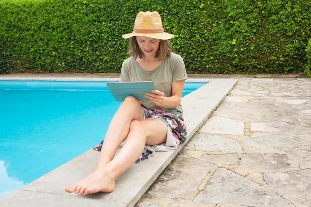 Glimlachende geconcentreerde vrouw die met tablet bij zwembad werken