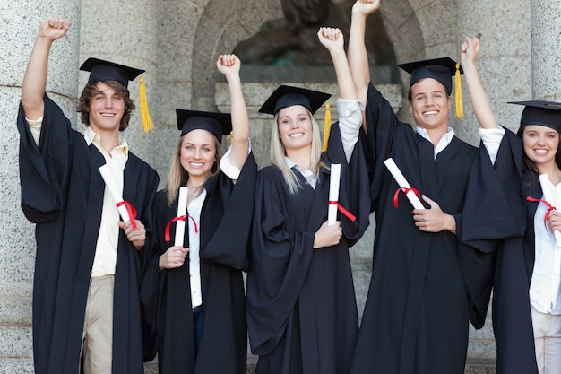 Glimlachende gediplomeerden die terwijl het opheffen van wapens stellen