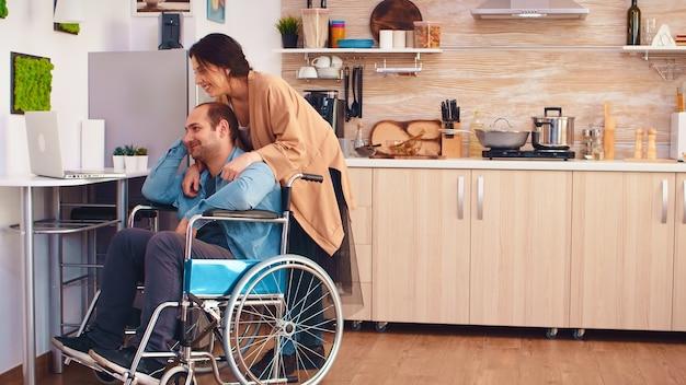 Glimlachende gehandicapte man in rolstoel en zijn vrouw tijdens een videogesprek op laptop in de keuken. zakelijke man met verlamming handicap handicap gehandicapte moeilijkheden met werken na ongeval met stagiair