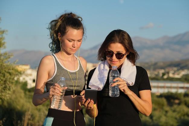 Glimlachende gelukkig pratende moeder en dochter tiener, ouder en kind samen joggen, ontspannen na het sporten drinkwater en smartphone kijken