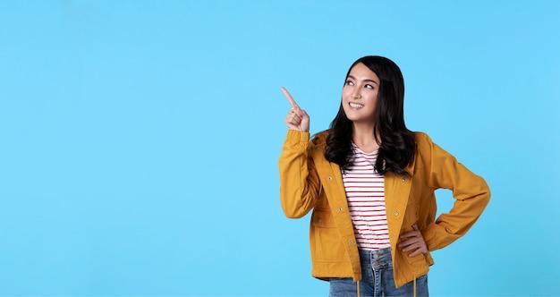Glimlachende gelukkige aziatische vrouw met haar vinger richten geïsoleerd op lichtblauwe bannerachtergrond met exemplaarruimte.