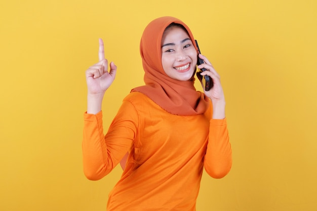 Glimlachende gelukkige aziatische vrouw met haar vinger wijzend geïsoleerd op lichtgele bannerachtergrond met hijab, pratend met mobiele telefoon