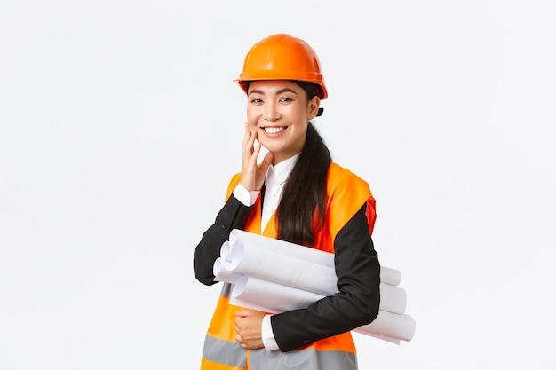 Glimlachende gelukkige aziatische vrouwelijke architect, bouwmanager in veiligheidshelm en jasje, draagt blauwdrukken van bouwproject en kijkt verrukt, rondt plan op tijd af, staande witte muur.