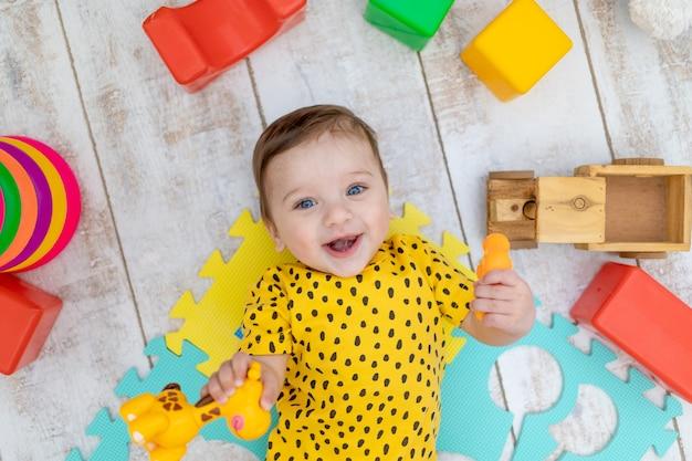 Glimlachende gelukkige babyjongen speelt in de kinderkamer in een gele bodysuit met fel kleurrijk speelgoed