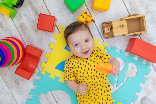 Glimlachende gelukkige babyjongen speelt in de kinderkamer in een gele romper met helder kleurrijk speelgoed