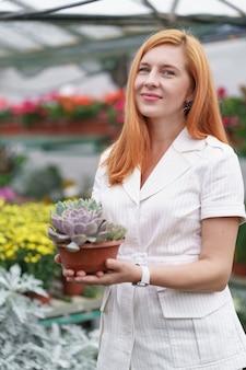 Glimlachende gelukkige bloemist in haar kwekerij staande met een ingemaakte combinatie van vetplanten in haar handen terwijl ze de tuinplanten in de kas neigt