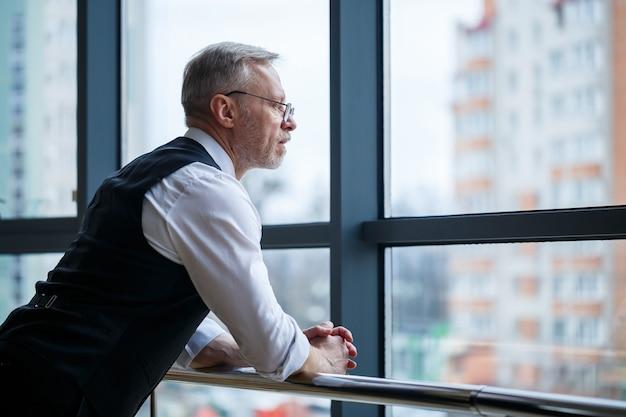 Glimlachende gelukkige directeur denkt aan zijn succesvolle loopbaanontwikkeling terwijl hij in zijn kantoor staat in de buurt van de achtergrond van een raam met kopieerruimte