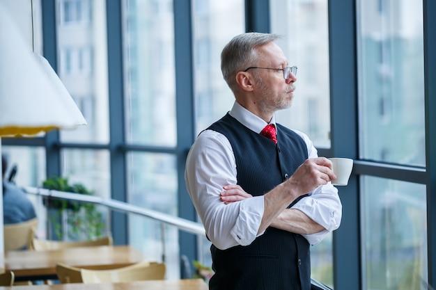 Glimlachende gelukkige directeur denkt aan zijn succesvolle loopbaanontwikkeling terwijl hij met een kopje koffie in zijn hand in zijn kantoor in de buurt van de achtergrond van een raam met kopieerruimte staat