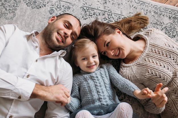 Glimlachende gelukkige familie die thuis op de vloer ligt