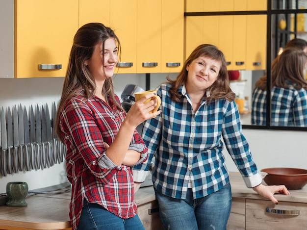 Glimlachende gelukkige familie moeder en dochter in de keuken