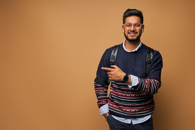 Glimlachende gelukkige indiase student met rugzak die zijn vinger op de muur wijst.