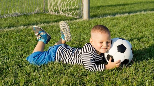 Glimlachende gelukkige jonge jongen die op groen gras bij een sportveld in avondlicht met een voetbalbal ligt
