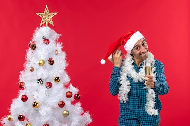 Glimlachende gelukkige jonge kerel die met de hoed van de kerstman speelt en een glas wijn opheft en klok die zich dichtbij kerstboom op rood bevindt te houden