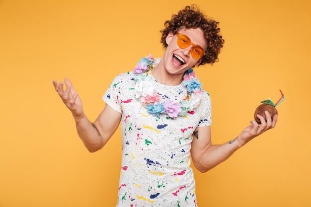 Glimlachende gelukkige jonge mens in zonnebril en strandslijtage