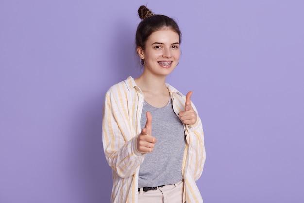 Glimlachende gelukkige jonge vrouw die op camera met wijsvingers richten