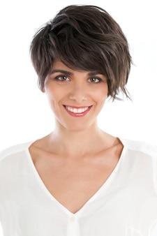 Glimlachende gelukkige jonge vrouw die op wit wordt geïsoleerd