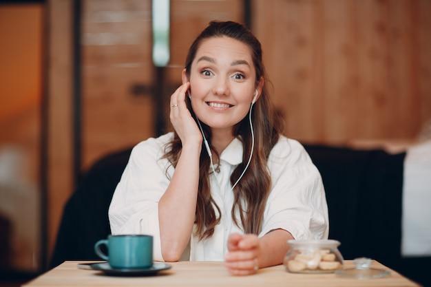 Glimlachende gelukkige jonge vrouw die thuis aan tafel zit achter een computerlaptop en praat over een videogesprek. meisje vrouw met draagbare mobiele koptelefoon online spreken op webcam binnenshuis.