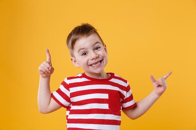 Glimlachende gelukkige jongen die vingers benadrukken op copyspace