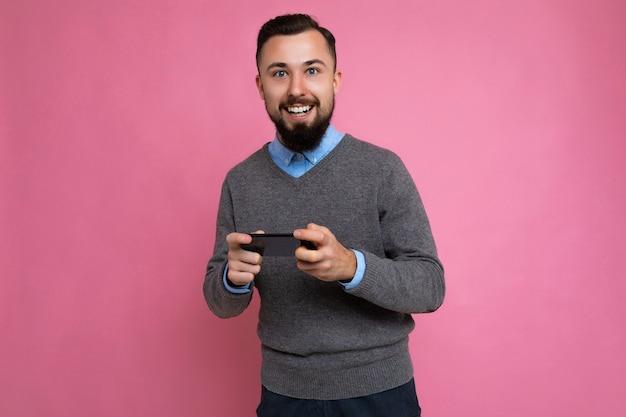 Glimlachende gelukkige knappe knappe brunet bebaarde jonge man met grijze trui en blauw shirt