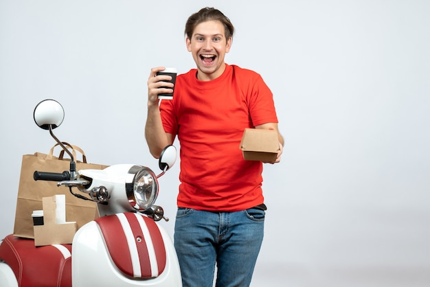 Glimlachende gelukkige leveringsmens in rode eenvormige status dichtbij autoped die kleine doos op witte achtergrond toont