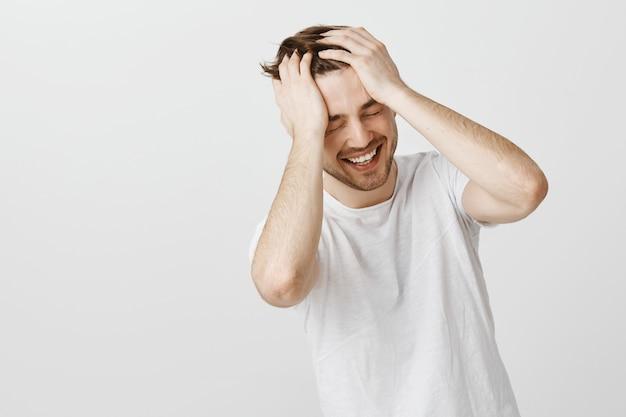 Glimlachende gelukkige man kan zijn eigen geluk niet geloven, zijn hand op het hoofd houden en lachen