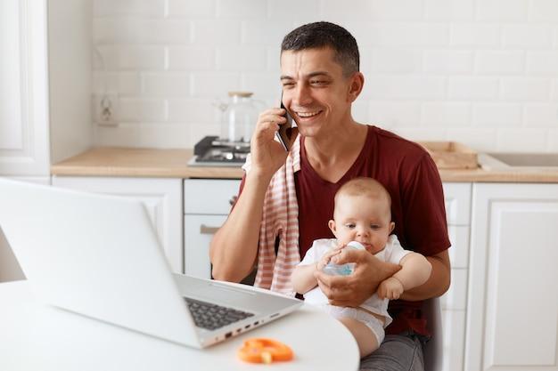 Glimlachende gelukkige man met een bordeauxrood casual t-shirt met een handdoek op zijn schouder, voor de baby zorgen en online werken vanuit huis, een prettig gesprek voeren met de klant of partner.