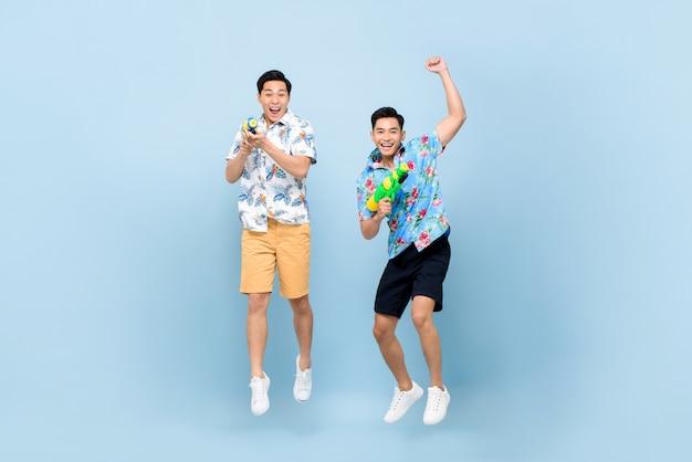 Glimlachende gelukkige mannelijke vrienden die met waterkanonnen spelen en voor songkran-festival in thailand en zuidoost-azië springen