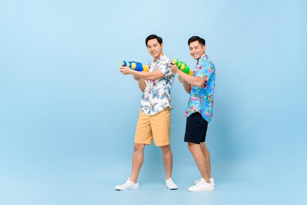 Glimlachende gelukkige mannelijke vrienden die met waterkanonnen spelen voor songkran-festival in thailand en zuidoost-azië