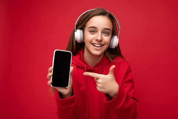 Glimlachende gelukkige mooie donkerbruine vrouwelijke tiener die rode hoodie draagt die op rode achtergrond wordt geïsoleerd