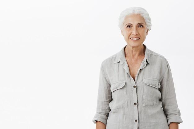 Glimlachende gelukkige oma die over witte achtergrond kijkt