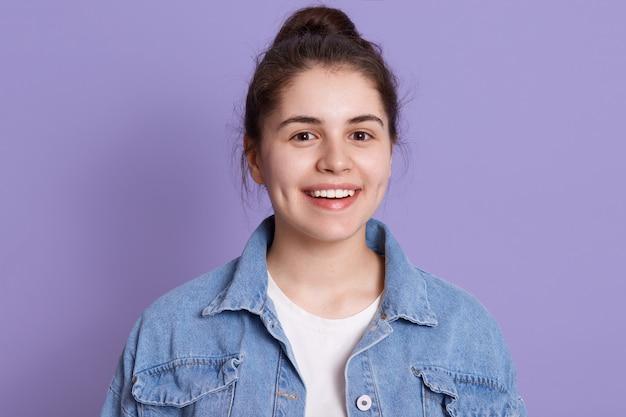Glimlachende gelukkige vrouw die denimjasje en wit overhemd draagt