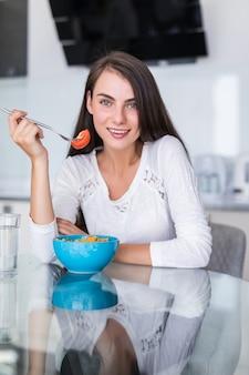 Glimlachende gelukkige vrouw die een ontspannend gezond ontbijt hebben die thuis bij keukenlijst zitten