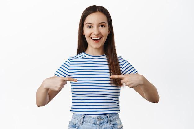 Glimlachende gelukkige vrouw die met de vingers naar het midden wijst, lege ruimte tegen haar borst en opgewonden kijkt, uitverkoop toont, over een witte muur staat