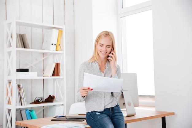 Glimlachende gelukkige vrouw die op mobiele telefoon praat en document vasthoudt terwijl ze op haar werkplek zit